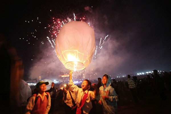 Students releasing lanterns during the opening ceremony of the Tazaungdaing Lighting Festival.  Every year in November as the full moon approaches, tens of thousands of people from all over the country gather in Taunggyi for the colorful hot-air balloons festival during which balloons lift fireworks or lanterns which illuminate the sky at night while balloons of all shapes are flown during the day, Taunggyi, northeastern Shan State, Myanmar