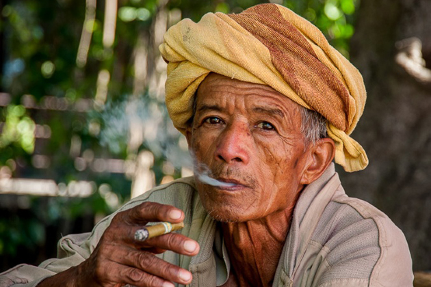 Burmese man smoking traditional handmade cigar