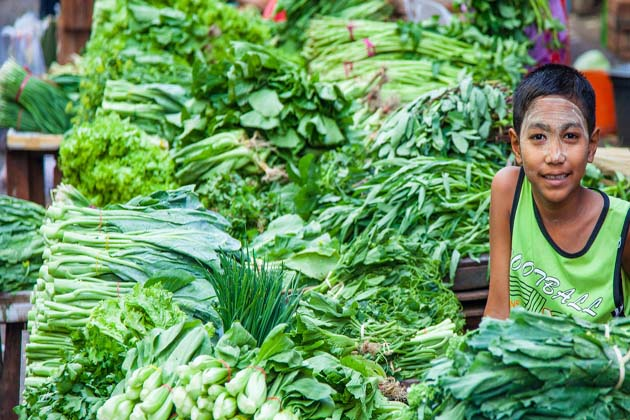 A Burmese boy selling vegetable with a smile on face