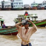 Burmese fisherman before diving trip on the bank of Yangon River