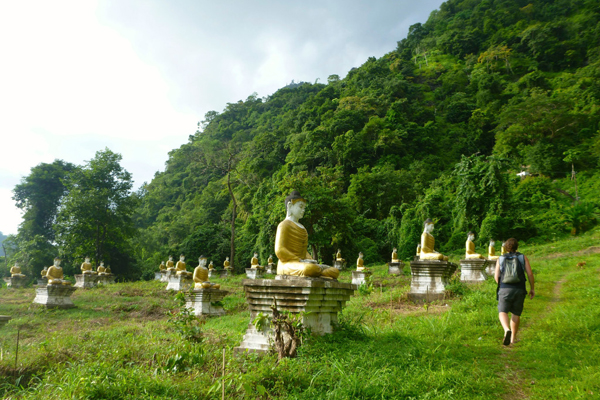 Walking past the seated Buddhas at up Mount Zwegabin, Hpa An, Myanmar