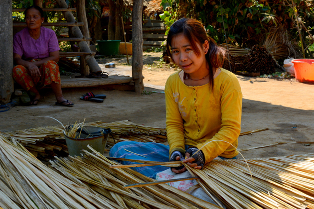 Girl with traditional thanaka weaving the palm leaves, Sagar on the banks of the Beluo Chaung