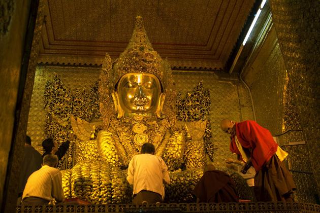 Mahanuni Buddha image covered by offered golden leaf