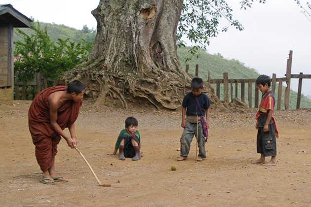 Monk and local children playing golf in Myanmar