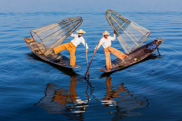 inle lake fishermen ride his boat by one leg