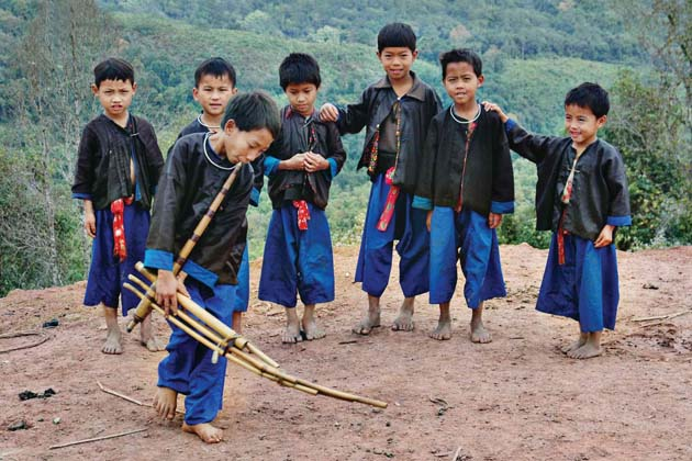 Lahu little boy is playing their traditional musical instrument