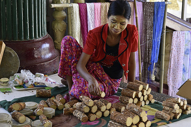 A Burmese woman sells thanakha in the market of Pakokku