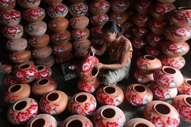 a local artisan is making a pot in the pottery workshop in Twante