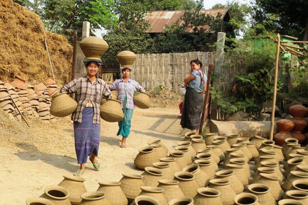 women carry pots on their head in yandabo pottery village